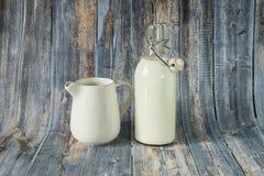 Leche fresca para el desayuno en una botella de cristal y un jarro abiertos para derramar la leche en un fondo de madera de sombr fotografía de archivo