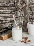 Leche y almendras, un libro, vidrios de la almendra en la tabla de madera ligera rústica Imágenes de archivo libres de regalías