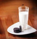 Leche y galletas en una tabla de madera Fotografía de archivo