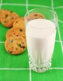 Leche y galletas, foco en la leche foto de archivo