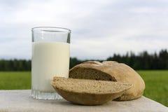 Leche y pan en un prado imágenes de archivo libres de regalías