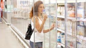 Lechería o ultramarinos de compra de la muchacha en el supermercado almacen de video