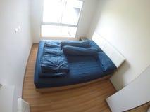 Lecho azul grande en dormitorio Imagen de archivo libre de regalías