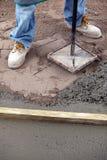 Lecho de la arena del apisonamiento del trabajador del constructor con una herramienta Fotos de archivo libres de regalías