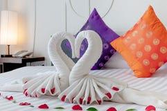 Lecho del hotel con papiroflexia del cisne Foto de archivo libre de regalías
