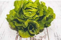 Lechuga verde jugosa fresca en la tabla vintage-diseñada Foto de archivo libre de regalías
