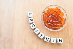 Lecithin gel pills in a round glass bowl and with the word Lecetin from the letters of cubes on a light wooden background. Soy royalty free stock image