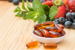 Lecithin gel vitamin supplement capsules. On wooden table Royalty Free Stock Photo