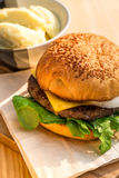 Leckerer Rindfleisch-und Käse Hamburgerplatz auf hölzernem Behälter neben Kartoffel Lizenzfreie Stockfotografie