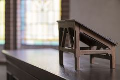 Lectern in an old church. Wooden lectern in an old church with stained glass windows in the background stock images