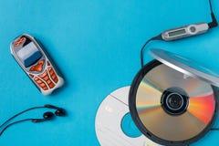 Lector de cd personal con el teléfono teledirigido y móvil en fondo azul imágenes de archivo libres de regalías