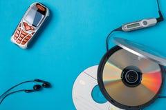 Lector de cd personal con el teléfono teledirigido y móvil en fondo azul imagen de archivo libre de regalías