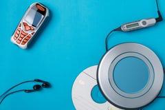 Lector de cd personal con el teléfono teledirigido y móvil en fondo azul foto de archivo libre de regalías