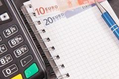 Lector de la tarjeta de cr?dito para la transacci?n cashless del pago, la libreta para las notas y el euro Concepto del asunto foto de archivo libre de regalías