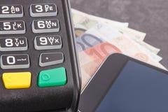 Lector de la tarjeta de cr?dito, tel?fono m?vil con tecnolog?a de NFC y euro de los curriencies Efectivo o transacci?n cashless d foto de archivo