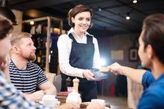 Lector de tarjetas feliz de la tenencia de la camarera de la señora mientras que huésped que paga con imágenes de archivo libres de regalías