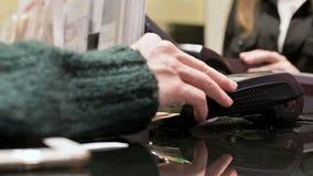 Lector de tarjetas terminal del primer para el pago con tarjeta de crédito La mano de la mujer introduce código del perno en el t almacen de video