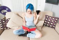 Lectura adolescente bastante femenina de los jóvenes en casa Fotografía de archivo