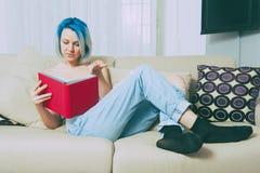 Lectura adolescente bastante femenina de los jóvenes en casa Fotos de archivo