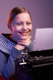 Lectura adolescente de la muchacha algo con sonrisa en su cara Fotografía de archivo