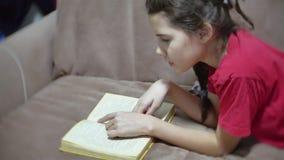 Lectura adolescente de la muchacha que se sienta en el sofá en el sofá niño de la muchacha que lee un libro que miente en dentro  almacen de metraje de vídeo