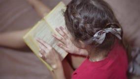 Lectura adolescente de la muchacha que se sienta en el sofá en el sofá niño de la muchacha que lee un libro que miente en un sofá metrajes