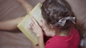 Lectura adolescente de la muchacha que se sienta en el sofá en el sofá niño de la muchacha que lee un libro que miente en un sofá almacen de metraje de vídeo
