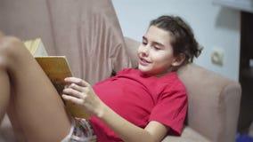 Lectura adolescente de la muchacha una sentada en el sofá en dentro el sofá niño de la muchacha que lee dentro un libro que mient metrajes