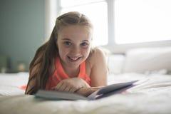 Lectura adolescente morena joven un libro en cama Imagen de archivo