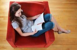 Lectura adolescente un compartimiento Foto de archivo libre de regalías