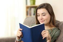 Lectura adolescente un libro de papel en un sofá Foto de archivo