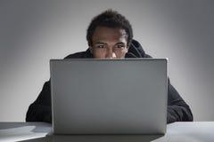 Lectura afroamericana joven del hombre del ordenador portátil fotografía de archivo
