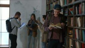 Lectura apuesta del estudiante masculino en biblioteca metrajes