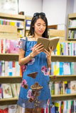 Lectura asiática de la muchacha en una librería Imágenes de archivo libres de regalías