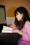 Lectura asiática de la muchacha en el escritorio, por el ordenador Foto de archivo