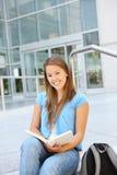 Lectura atractiva de la mujer en la biblioteca de escuela Imagen de archivo libre de regalías