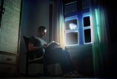 Lectura bajo claro de luna Foto de archivo libre de regalías