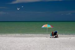 Lectura bajo el parasol de playa Imágenes de archivo libres de regalías