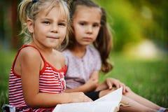 Lectura bonita de dos pequeña muchachas imagenes de archivo