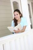 Lectura bonita de la muchacha en el pórtico casero Imagen de archivo