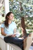 Lectura bonita de la muchacha en el pórtico casero Imágenes de archivo libres de regalías