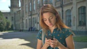 Lectura bonita de la mujer joven del jengibre del teléfono y mirada de la cámara con la emoción sorprendida, sonrisa, colocándose metrajes