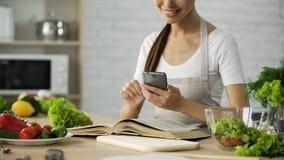 Lectura bonita de la mujer que cocina el libro y calorías calculadoras en el smartphone app Imágenes de archivo libres de regalías
