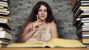 Lectura cansada del estudiante entre los libros Mujer joven pensativa que se sienta en la tabla con la pila de libro y que sigue  almacen de metraje de vídeo