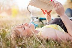 Lectura caucásica hermosa de la mujer al aire libre Imagen de archivo libre de regalías