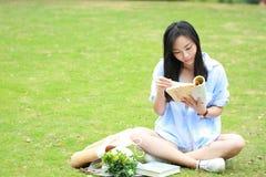 Lectura china de la muchacha en parque La mujer joven hermosa rubia con el libro se sienta en la hierba Fotos de archivo libres de regalías