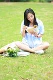 Lectura china de la muchacha en parque La mujer joven hermosa rubia con el libro se sienta en la hierba Imágenes de archivo libres de regalías