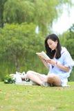 Lectura china de la muchacha en parque La mujer joven hermosa rubia con el libro se sienta en la hierba Fotografía de archivo libre de regalías