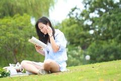 Lectura china de la muchacha en parque La mujer joven hermosa rubia con el libro se sienta en la hierba Imagen de archivo libre de regalías
