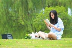 Lectura china de la muchacha en parque La mujer joven hermosa rubia con el libro se sienta en la hierba Fotografía de archivo